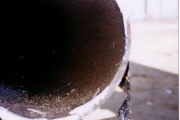 Pipeline cut out prior to cleaning. Note the oil layer.